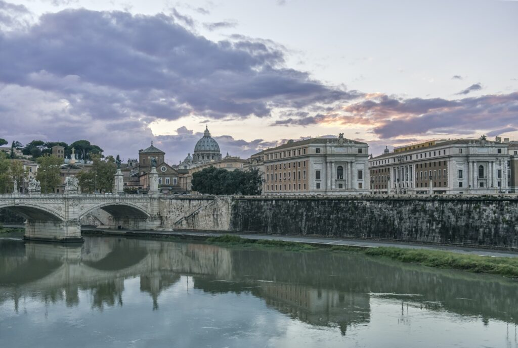 Ornate buildings and bridge reflecting in still river, Rome, Italy